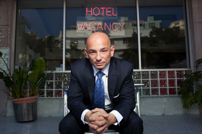 Hotel Impossible's Anthony Melchiorri poses in front of a hotel with some rooms for rent. (Photo Courtesy of the Travel Channel.)