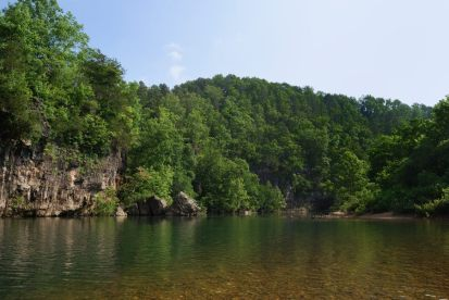 Photograph showing the swimming hole and bluff at the Blue Spring Campground, Jack's Fork river on the Ozark National Scenic Riverway.