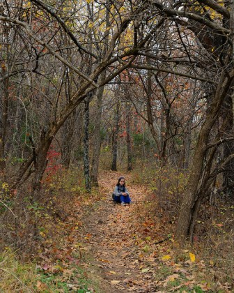 Girl sitting in the middle of the Sac River Trail in the fall, surrounded by trees.