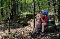 Teen girl wearing backpack and leaning on hiking pole is pictured seated on a rock in Piney Creek Wilderness as she rests during a hike during a backpacking trip.
