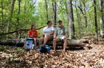 A girl, woman, and man sitting on a log for a picture during a spring backpacking trip in Piney Creek Wilderness in the southern Missouri Ozarks.