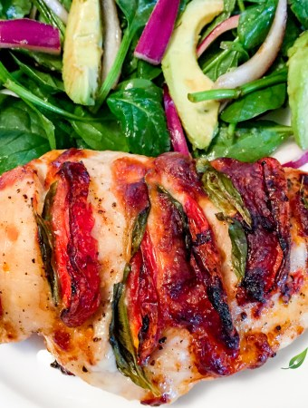 Hasselback Caprese Chicken with a fresh garden salad on a white plate