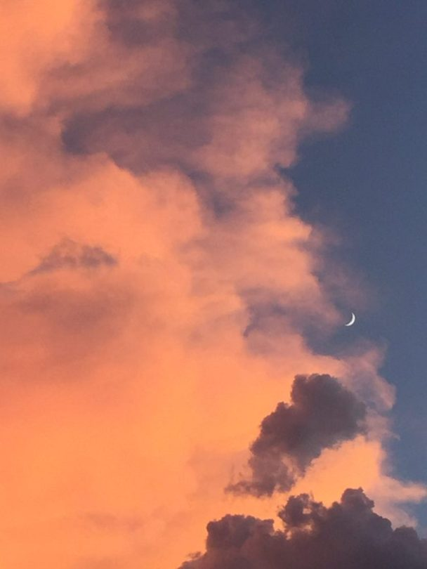 A sliver of the moon sets in the west, at sunset, behind monsoon clouds, in Tucson. Taken by Ralph Philabaum, Philabaum Professional Painting, Tucson, AZ