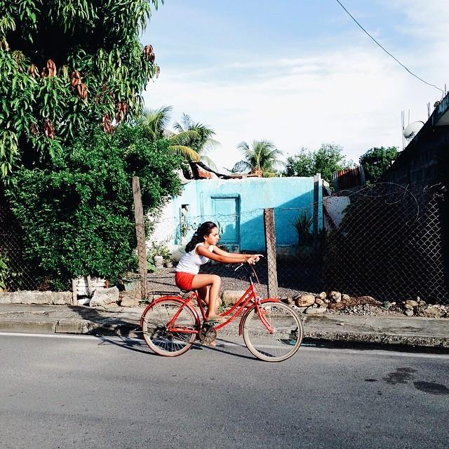 Niña en bicicleta frente a casita azul