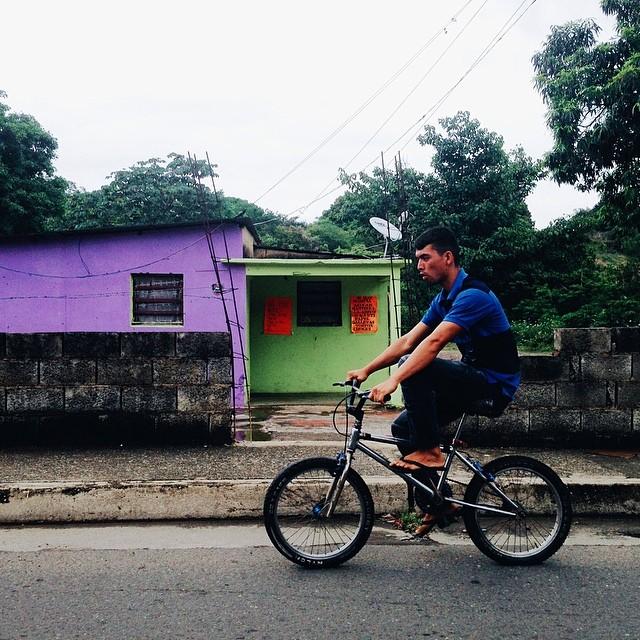 Chico en bicicleta frente a casita violeta y verde