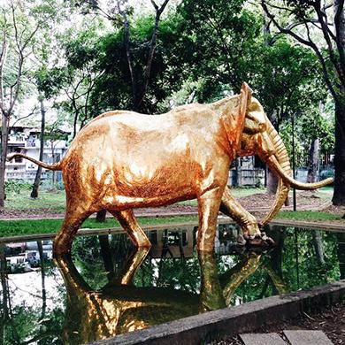 Un elefante dorado cruzando la fuente del parque