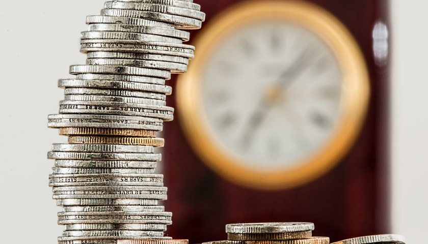 stack of coins in focus with clock in background that is out of focus