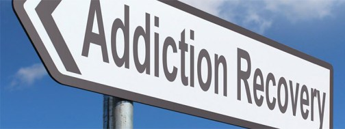 photo of road sign with blue sky background reading Addiction to Recovery.