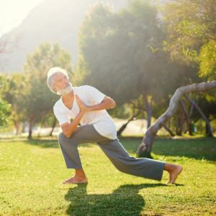 Man doing yoga in the grass