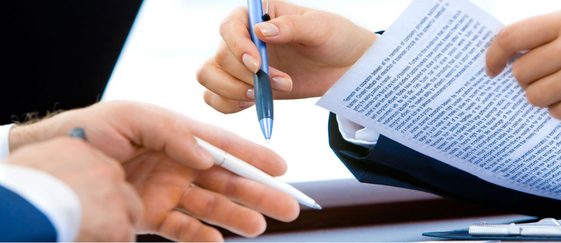 two people hold pens over a medical plan contract as they discuss renewing insurance