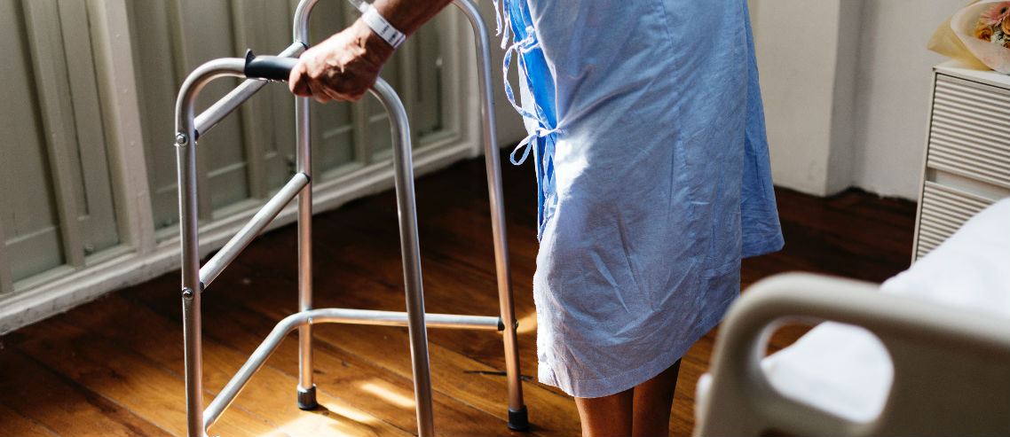 an elderly patient stands by a hospital bed assisted by a walking frame indicating the importance of understanding uae health insurance for seniors