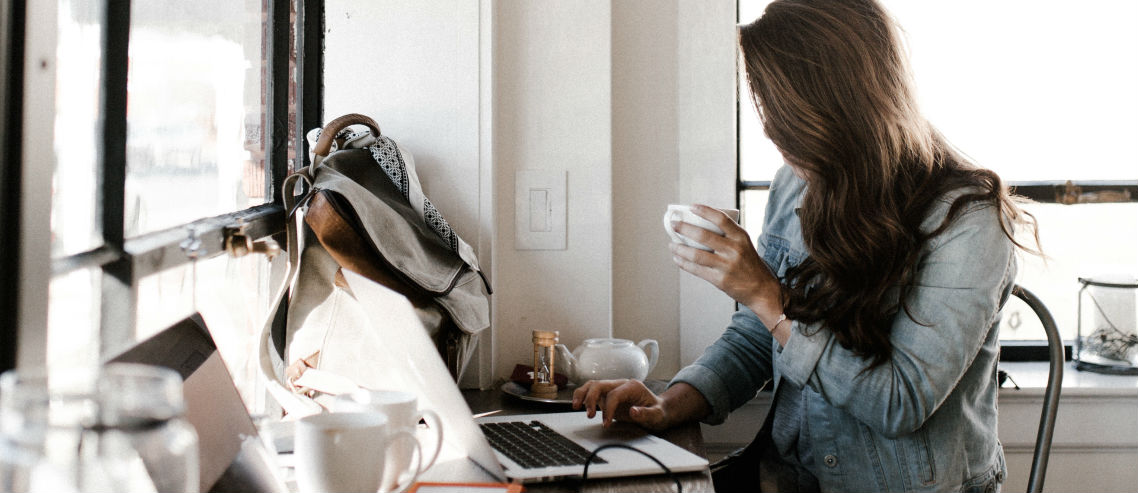 a businesswoman sits at a hot desk with a laptop and a coffee, symbolizing flexible work arrangements and the need to consider part time employee benefits