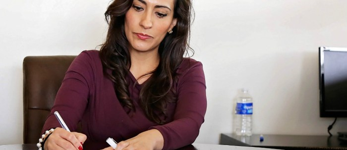 a businesswoman signs a form, potentially granting her part time employee benefits in a flexible role