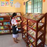 a young woman checks out the book selection in a library room to read and pacific prime built in laos