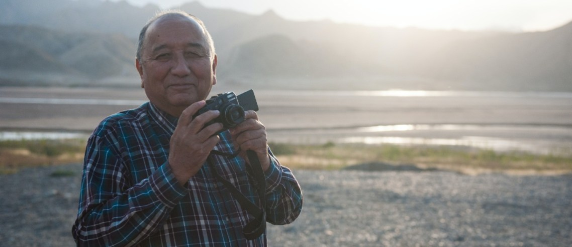 Old man traveling and taking pictures. He is healthy and happy because he takes good care of himself in retirement.