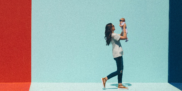 mother joyously carries her baby in front of a red, white and blue painted wall, representing the journey of maternity benefits for employees