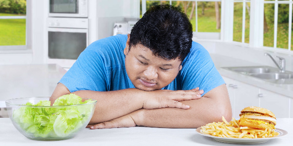 a large asian man sits with his head in his hands as he weighs up whether to eat lettuce or a plate full of chips and a burger, representing obesity in hong kong