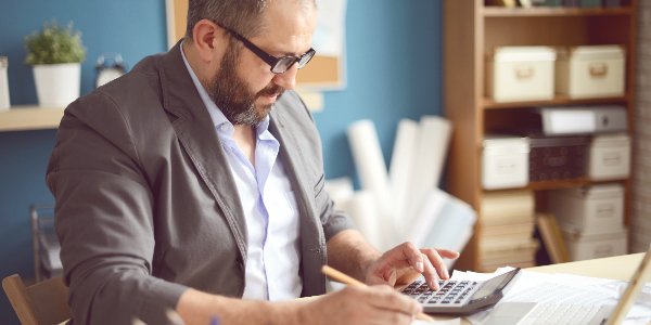 a male office manager works through group insurance plans information to calculate if his company is getting the best deal