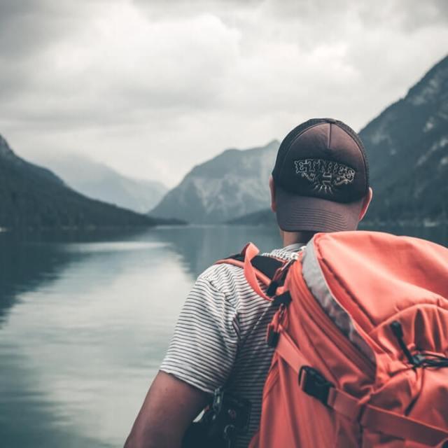 Personne avec sac a dos devant lac et montagne