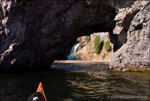 Kayaking through a sea arch at the Manitou River.