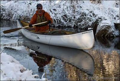 Canoeing on a calm stream in snow.