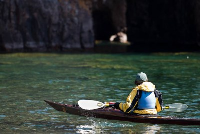 Kayaker looking into a sea cave on Lake Superior.