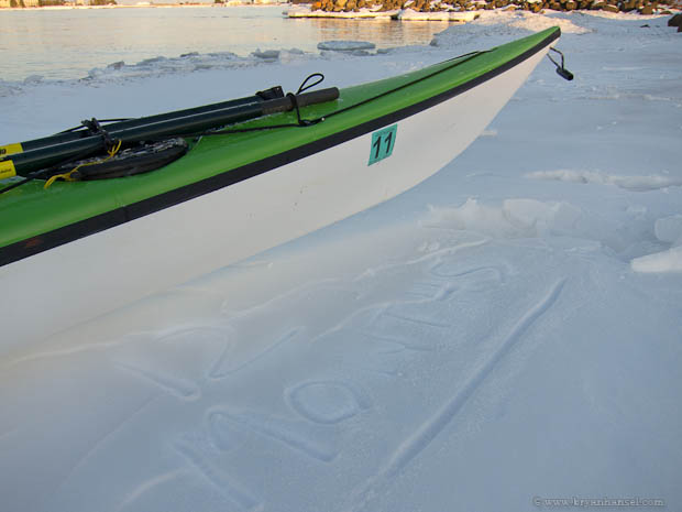 Kayak and 12 months etched out of snow.