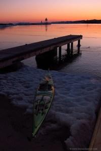 Kayak sitting on ice at sunset
