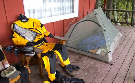 Kayaking expedition drysuit and tent on a porch