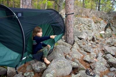kid sitting in a camping hammock