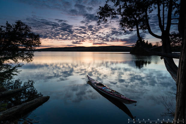 A sea kayak on Two Island Lake in Cook County, Minnesota. The clouds reflect in the calm water at sunset.