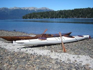 two skin on frame kayaks on beach