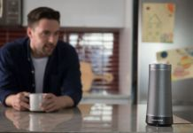 A man looking at his Harmon Kardon Invoke