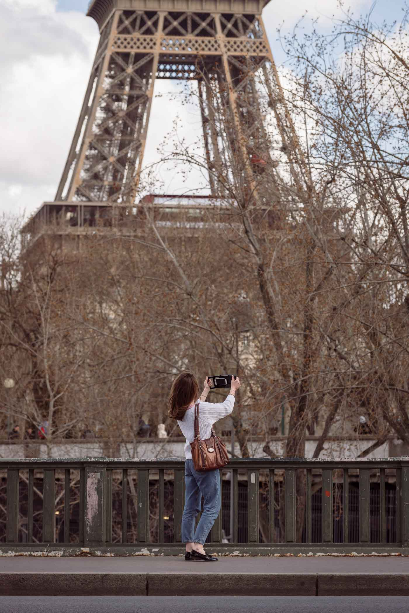 lifestyle photoshoot in Paris France for iOgrapher, model using iPhone filming case on bridge in front of Eiffel Tower and trees