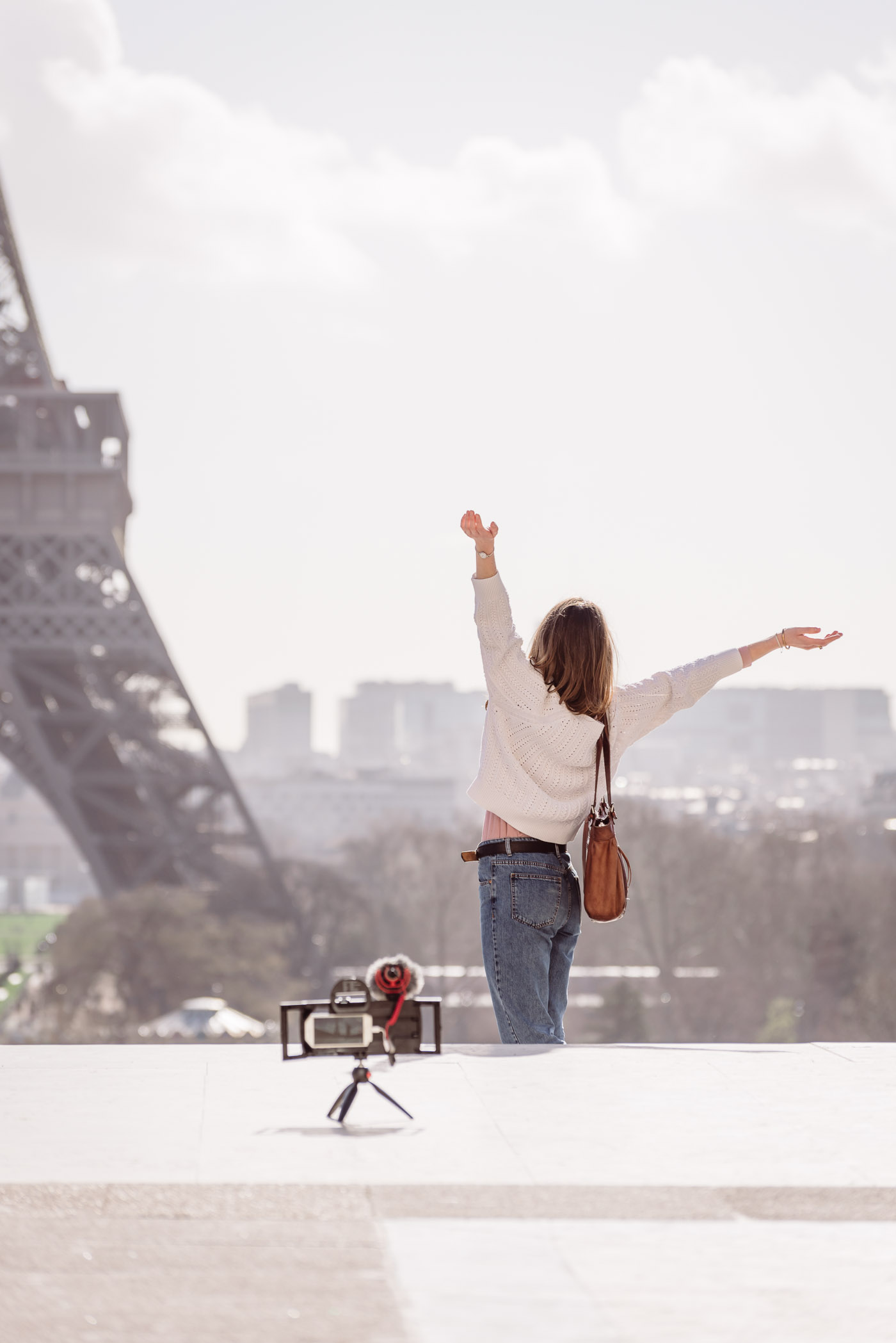 lifestyle photo of woman using iphone filming equipment and tripod in front of the Eiffel Tower