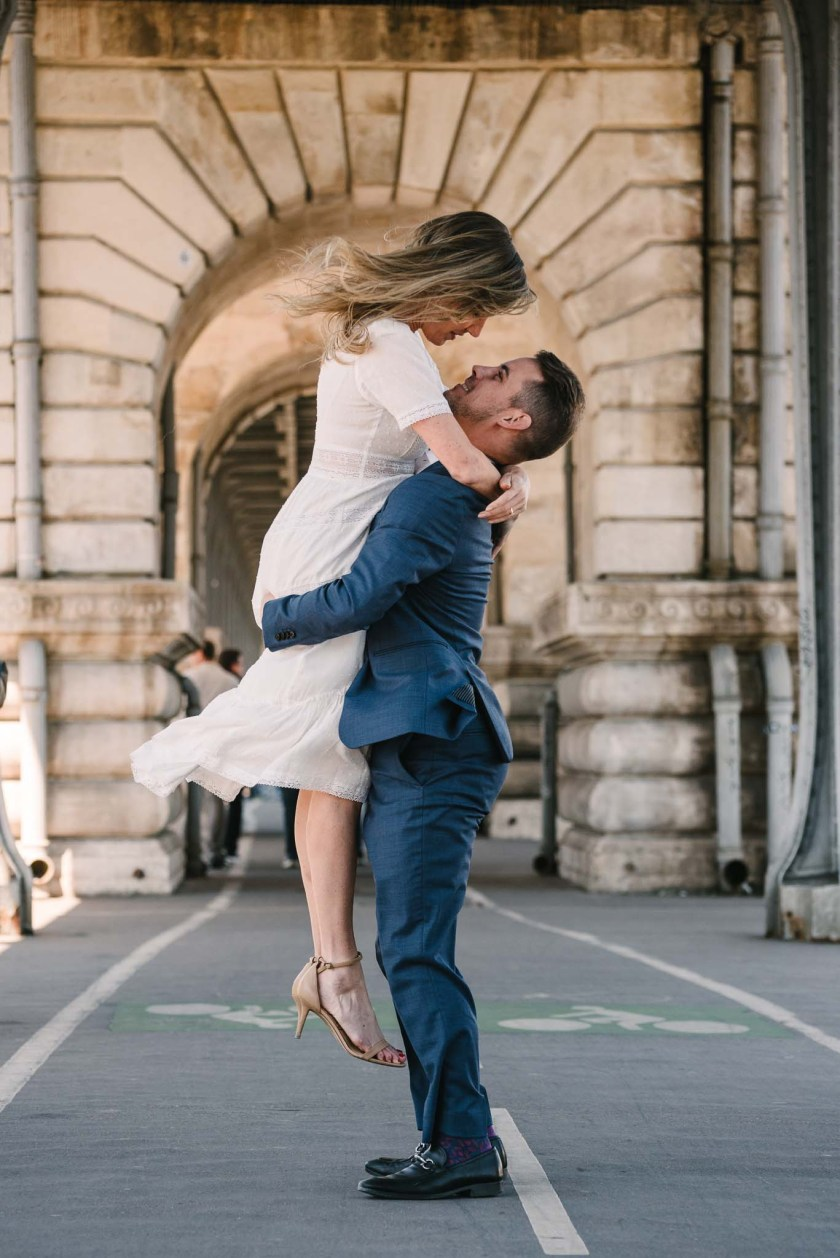 Romantic photo of an elopement in Paris with the groom picking the bride up to kiss her on the Bir-Hakeim bridge in Paris