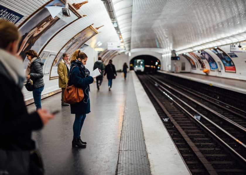 Woman in a blue coat and purse reading a book and listening to music while waiting for the metro in the Saint-Sébastien - Froissart station in Paris, France