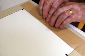 Press down on the tape along the edge of the frame and onto the backing board