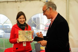 Judge Nick Holmes discusses Second prize winning painting 'Blakeney Hard' by Artist Sam Robbins. Photo by Katy Jon Went