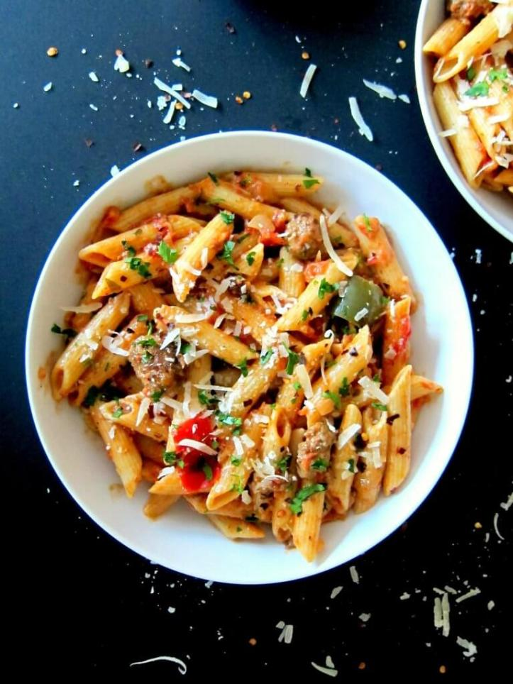 Instant Pot Pasta - Penne with Sausage in Tomato Cream Sauce, with red and green peppers, sprinkled with parmesan, in white bowl on black background - From Paint the Kitchen Red