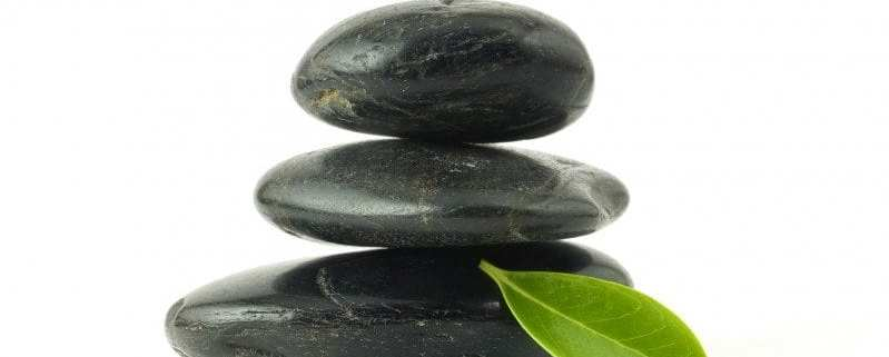 Pebbles stack and green leaf