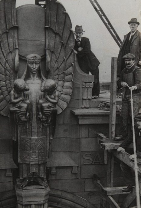 Men working at the top of the Russell Institute building, showing the detailed stonework.