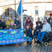 The group from the Disability Resource Centre gathered alongside the artists and musicians from Brass Aye to see the flag raised