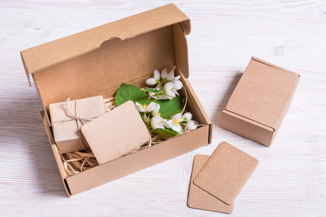 Custom corrugated box with inserts. A flower and tied soap is contained within.