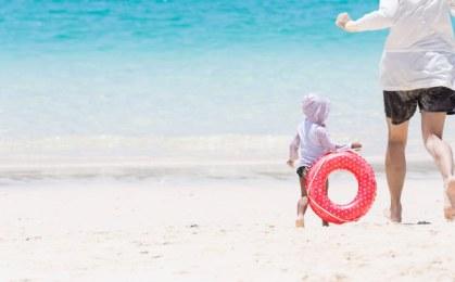 美しい海で追いかけっこする親子