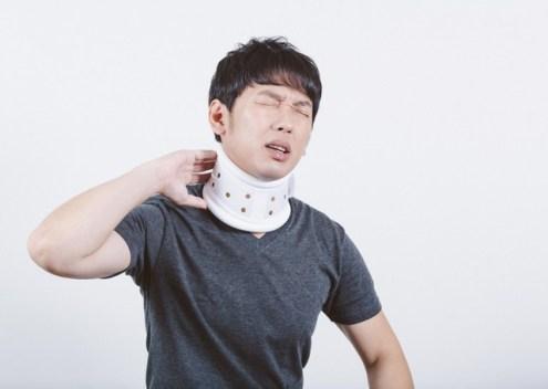交通事故のむち打ちで首にコルセットを巻く男性