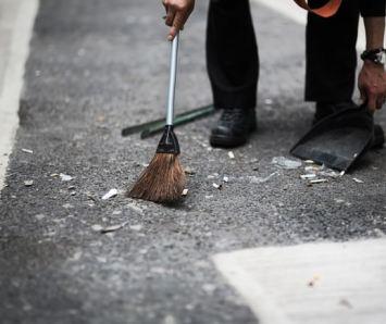 渋谷の街をチリトリとホウキで清掃する人