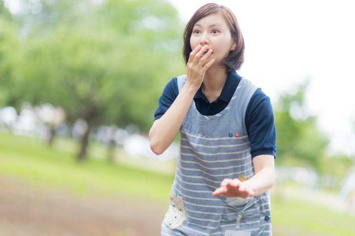 「思いがけない出来事に驚き声も出ない介護士の女性」[モデル:yumiko]