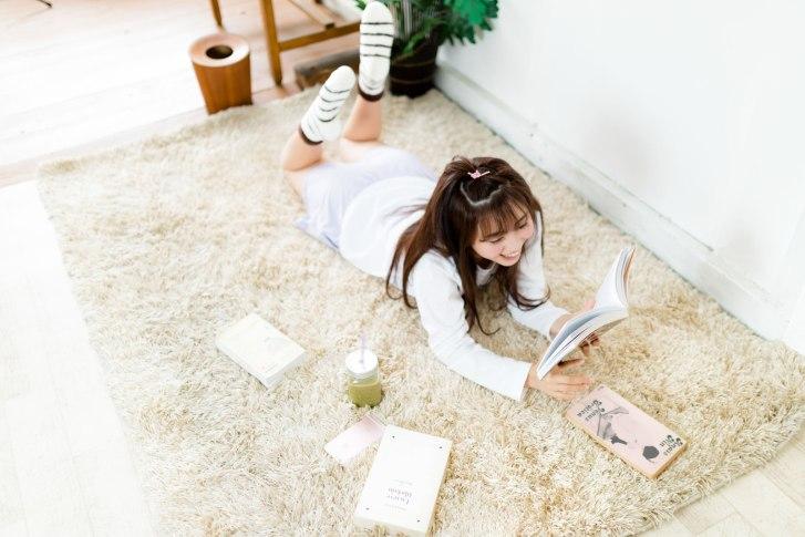 「グリーンスムージーを飲みながら本を読む部屋着女子」[モデル:河村友歌]