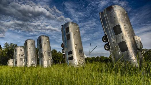 Photo of several old Airstream trailers buried end-up in a field
